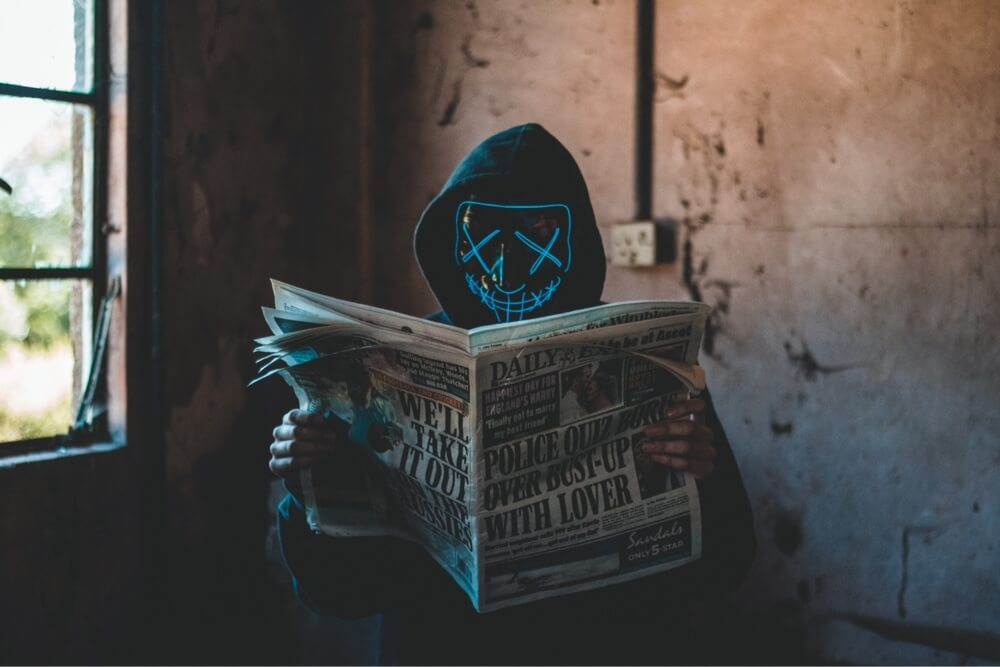 Person in mask read newspaper